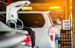 在que的车库等待停放的汽车变动轮胎和维护的 自动服务业 汽车零件概念 汽车开放树干 免版税库存照片