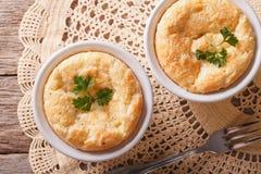 在ramekens特写镜头的被烘烤的乳酪蛋白牛奶酥 水平的顶视图 库存照片