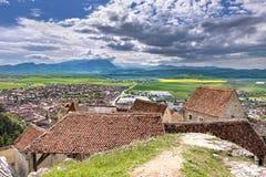 在Rasnov市的春天视图,在布拉索夫县(罗马尼亚),有Rasnov城堡的老房子的前景和皮亚特拉的 免版税库存照片