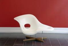 在redwall前面的一把白色设计椅子 库存照片