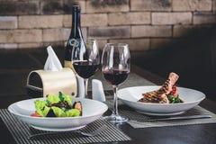在resraurant的浪漫晚餐 两开胃盘和两 免版税库存图片
