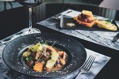 在resraurant的浪漫晚餐 两开胃盘和gla 免版税库存图片