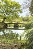 在Rikugien公园池塘的日本石桥梁在Bunkyo dis 库存图片