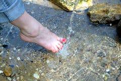 在rinning的户外水特写镜头下的女性赤脚 库存照片