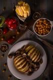 在Roasted土豆的在葡萄酒的顶视图用荷兰扁圆形干酪和蒜味咸腊肠上用小蕃茄 库存图片
