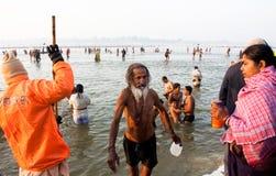 在Sangam水中沐浴的年长人 图库摄影