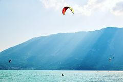 在Santa Croce湖上的五颜六色的滑翔伞形成 免版税库存图片