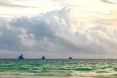 在sauset热带蓝色海,菲尔天际的三艘帆船  免版税库存照片