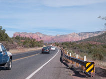在Sedona亚利桑那附近的红色岩石与汽车通行 免版税库存照片