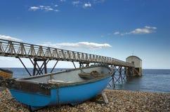 在Selsey比尔救生艇岗位的蓝色渔船 库存照片