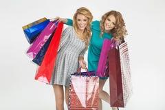 在shoping期间的两名快乐的妇女 免版税库存照片