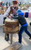在Shrovetide娱乐节目期间,人给男孩展示老手工制造磨房工作  免版税库存图片