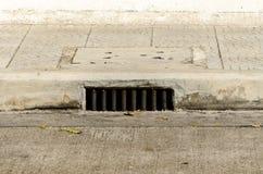 在sidwalk 0n混凝土路下的下水道出入孔 库存照片