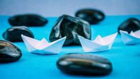 在Sigle文件的两艘白皮书船在蓝色背景的抽象黑岩石石头之间 射击端 库存图片