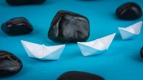 在Sigle文件的两艘白皮书船在蓝色背景的抽象黑岩石石头之间 库存照片