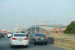 在Sirat高速公路的汽车通行在轰隆苏盛大驻地工地工作前面 图库摄影