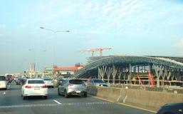 在Sirat高速公路的汽车通行在轰隆苏盛大驻地工地工作前面 免版税库存图片
