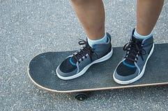 在skateboad的儿童的腿在街道上 免版税库存图片