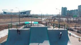 在skatepark的鸟瞰图 今后乘坐两个专业人的开始骑从舷梯的上面的自行车和 影视素材
