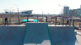 在skatepark的鸟瞰图 骑从舷梯的上面的两个专业人开始自行车 影视素材