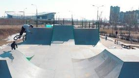 在skatepark的鸟瞰图 骑自行车的两个专业人在舷梯 训练他们的技能 影视素材