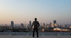 在skyscrabber,企业概念屋顶上面的商人立场  免版税库存照片
