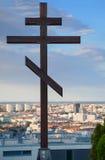在SlavÃn战争纪念碑前面的东部Orthhodox十字架立场和背景是巨大的布拉索夫都市风景,地平线 库存照片