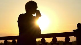 在Slo Mo供以人员从一纸杯的饮料咖啡并且享受在一座桥梁的日落 股票视频