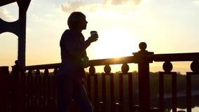 在Slo Mo供以人员从一纸杯的饮料咖啡并且享受在一座桥梁的日落 股票录像
