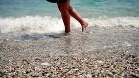 在slowmo,女孩的腿在与小卵石的海滩去,她的腿由与泡沫的小波浪洗涤 股票录像