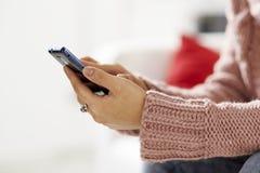 在smarthphone的亚洲女孩读书sms 图库摄影