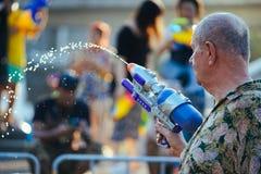 在Songkran期间,一个人演奏与他的水枪的水 免版税图库摄影