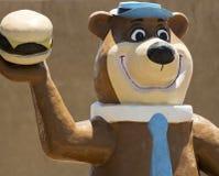 在Sparkys的一个信奉瑜伽者熊形象,在舱口盖的路旁吸引力 库存图片
