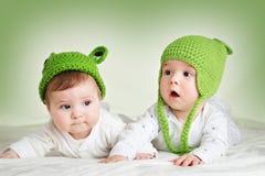 在spft毯子的青蛙帽子的两个逗人喜爱的婴孩 免版税库存图片