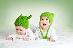 在spft毯子的青蛙帽子的两个逗人喜爱的婴孩 图库摄影