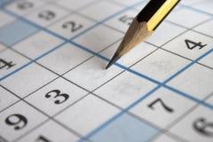 在Sudoku难题栅格板料的铅笔 库存照片