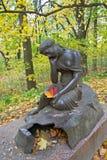 在Sukhanovo雕刻`有一水罐`的女孩与秋天叶子 免版税库存照片