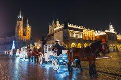 在Sukiennice前的用马拉的支架在主要集市广场在克拉科夫,夜视图,波尔布特 库存照片