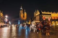 在Sukiennice前的用马拉的支架在主要集市广场在克拉科夫,夜视图,波尔布特 库存图片