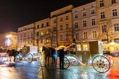 在Sukiennice前的用马拉的支架在主要集市广场在克拉科夫,夜视图,波尔布特 免版税库存照片