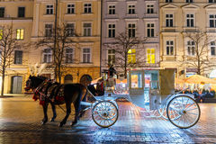 在Sukiennice前的用马拉的支架在主要集市广场在克拉科夫,夜视图,波尔布特 免版税库存图片