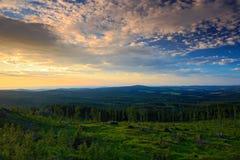 在Sumava山的丰富多样的早晨日出,砍在小山的森林,在天空, Knizeci Stolec,捷克Repu的好的云彩下 免版税库存图片