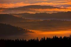 在Sumava山的日落 冷的早晨在Sumava国家公园、小山和村庄雾的和霜,有薄雾的看法在捷克土地 免版税库存照片