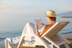 读在sunbed的女孩一本书 免版税库存照片