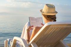 读在sunbed的女孩一本书 免版税库存图片