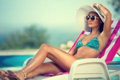 在sunbed的比基尼泳装的可爱的女孩 免版税库存图片