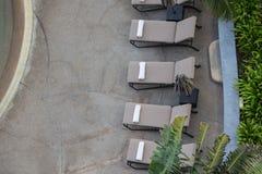在sunbeds的白色毛巾卷在与拷贝空间的游泳池 免版税库存照片