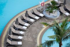 在sunbeds的白色毛巾卷在游泳池 库存图片
