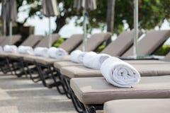 在sunbeds的白色毛巾卷在游泳池 免版税库存照片