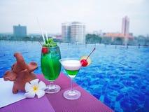 在swimmimg水池的鸡尾酒杯有城市视图 免版税库存照片